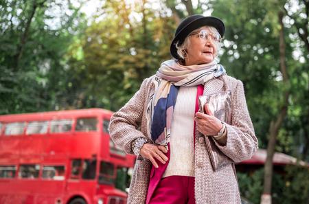 Zekere rijpe vrouw die op iemand op straat wacht