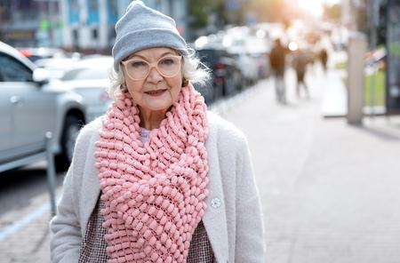 Joyful mature lady enjoying walk on street Imagens