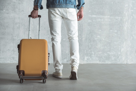 Travel concept. Close-up back view of traveler man legs walking with yellow suitcase. Gray wall in background. Copy space in the right side
