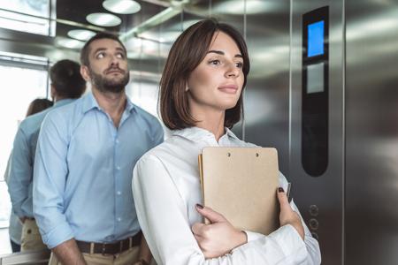 비즈니스 커플 엘리베이터에 상승하고있다
