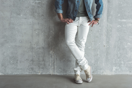 Stylish and confident. Close-up of crossed legs of elegant man. He is leaning on wall and holding hands on hips. Copy space in the left side Фото со стока
