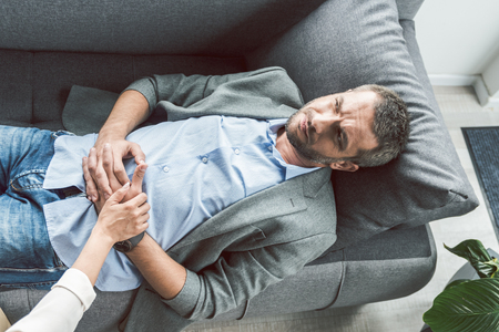 Sad man having session of psychoanalysis