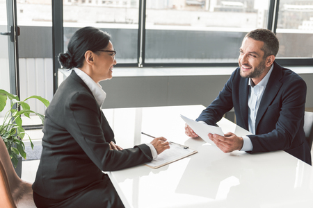 Cheerful businesswoman telling with male Banco de Imagens