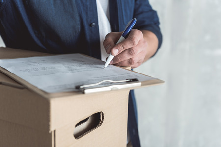 Place for sign. Close-up of hand with pen of professional courier who is holding cardboard box and folder with document. He is putting his signature while delivering personal order