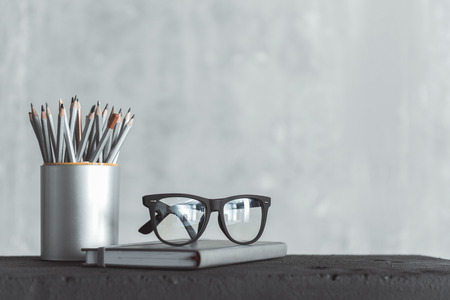 Prepared for work. Close-up of stylish eyeglasses of professional employee is on notepad and box of pencils is near. Gray wall in background. Copy space in the right side