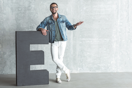 Positive guy in glasses is posing against gray wall