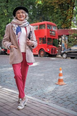 Vrolijke rijpe vrouw die zich dichtbij weg in stad bevindt Stockfoto