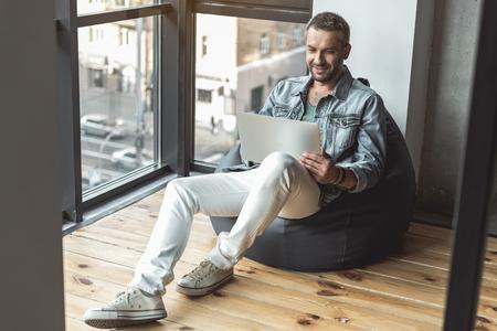 Joyful attractive guy is laboring on computer Zdjęcie Seryjne