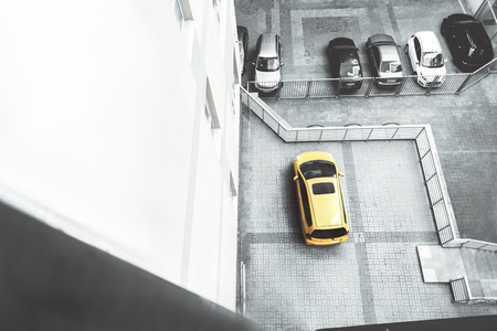Yellow element. Top view of bright car is on parking among black and white autos. Copy space in the left side