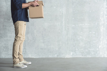 Good service. Close up of guy is holding box while delivering parcel to client. He is standing against gray wall background. Copy space in the right side