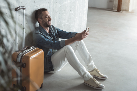Positive adult man is holding smartphone