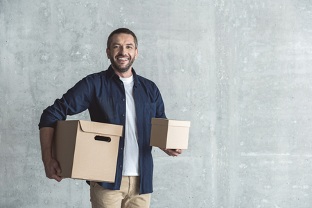 Cheerful bristled courier is holding cardboard boxes