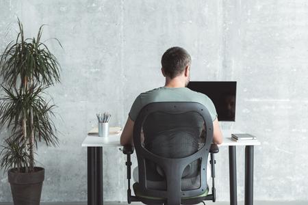 숙련 된 남자가 사무실에서 일하고있다. 스톡 콘텐츠