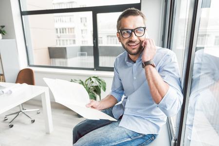 陽気な笑みを浮かべて男のオフィスで携帯電話を使用して