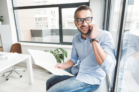 Cheerful smiling man using phone in office Banco de Imagens