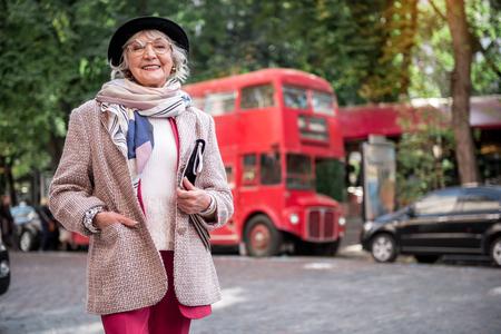 Opgewekte hogere dame die zich op straat bevindt