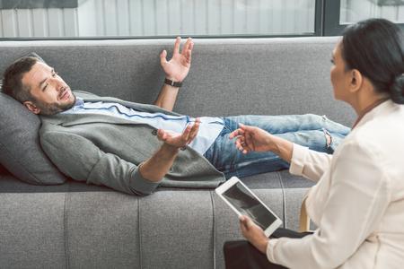 Bewildered man visiting female psychologist