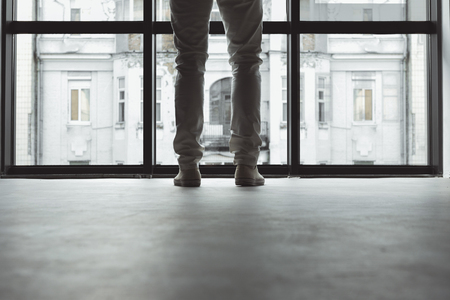 Close-up of legs of stylish elegant man. He is standing against big window with city landscape. Copy space Фото со стока