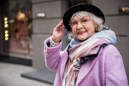 Joyful senior lady standing in fashionable clothing Standard-Bild