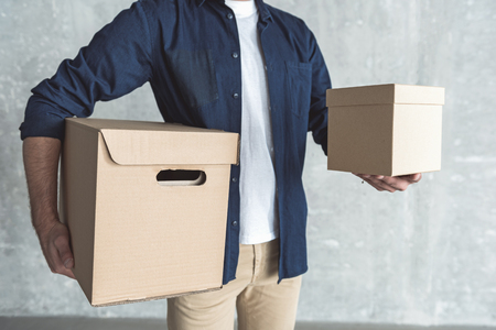 Courier service concept. Close-up of two cardboard boxes in hands of professional courier who is delivering purchases. He is standing against gray wall Banco de Imagens - 88404966