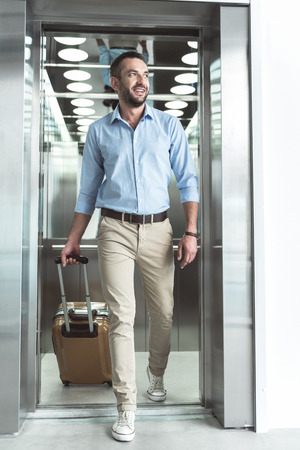 Joyful stylish guy with stubble is exiting from lift