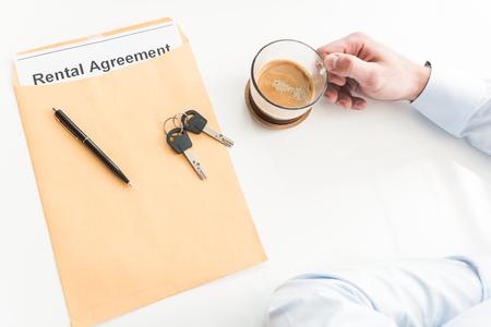 Top view keys, pen situating on rental agreement. Man arm holding mug of beverage. Break concept. Close up