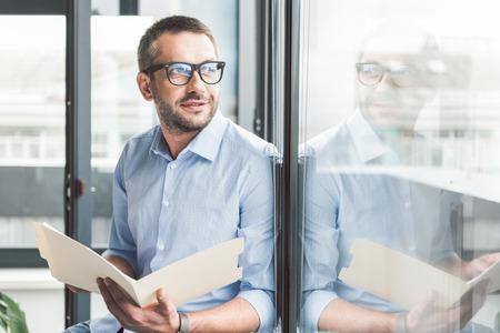 Joyous smiling man keeping papers
