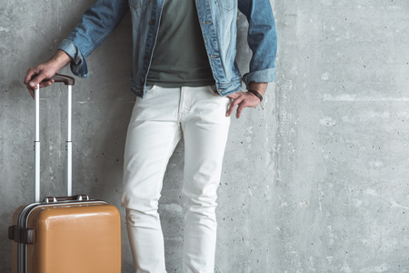 Start of vacation. Close-up of trendy elegant man is standing with suitcase against gray wall. Copy space in the right side