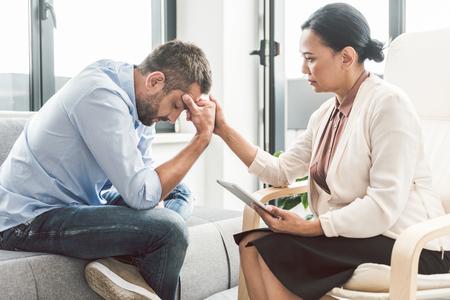 Serious female psychologist sitting near man Stock Photo