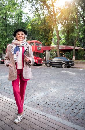 Gelukkige oude vrouw in modieuze kleding op straat Stockfoto