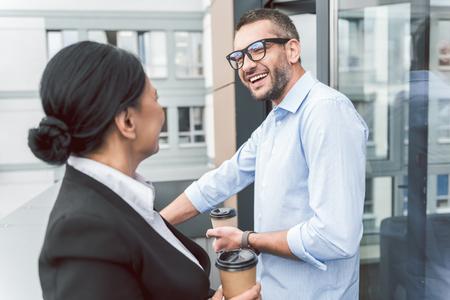 Hilarious smiling man standing near colleague Banco de Imagens