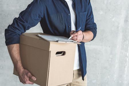 Serviço completo. Close-up da caixa de cartão nas mãos do correio que está assinando originais ao enviar a ordem pessoal do cliente. Parede cinza no fundo. Conceito de entrega Foto de archivo - 88405236