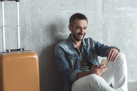 Charming elegant guy with stubble is holding mobile phone