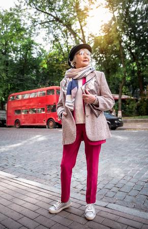 Nadenkende rijpe elegante dame die zich in stad bevindt