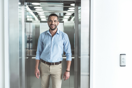 Pleasant cute guy is posing against modern lift Stock fotó