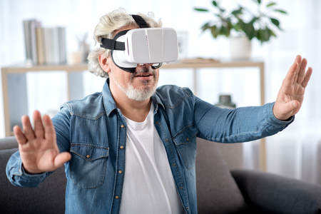 Blije rijpe mens die op virtuele werkelijkheidshoofdtelefoon letten