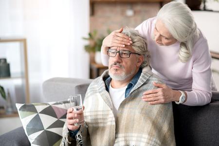 Rijpe vrouw die voor haar zieke echtgenoot zorgt Stockfoto