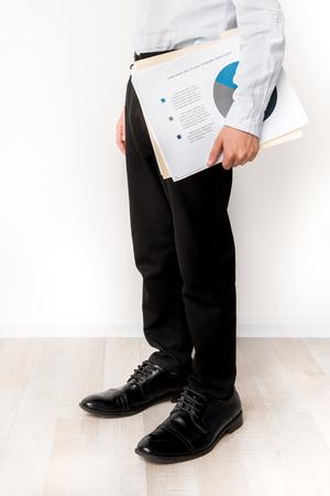Kleine voeten in groot schoenenconcept. Close-up van de benen van de kleine jongen draagt zwarte broek en permanent in volwassen laarzen terwijl belangrijke documenten
