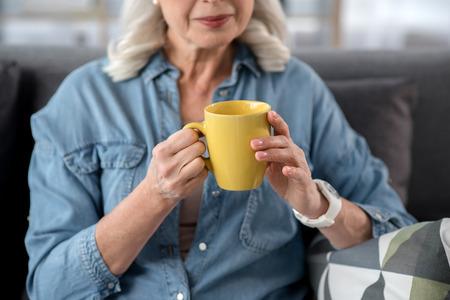 Cheerful mature lady drinking mu of beverage Stock Photo