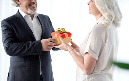 Happy senior husband handing over present to his wife Stock Photo