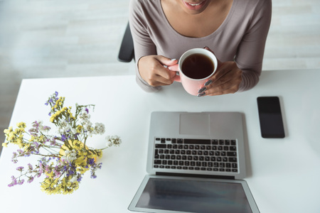 Beaming woman tasting beverage at desk