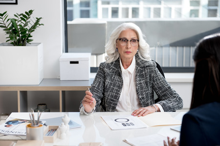 Pensive aged lady is laboring with documents Stock Photo