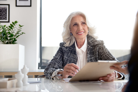 Joyful gorgeous old woman is holding documents
