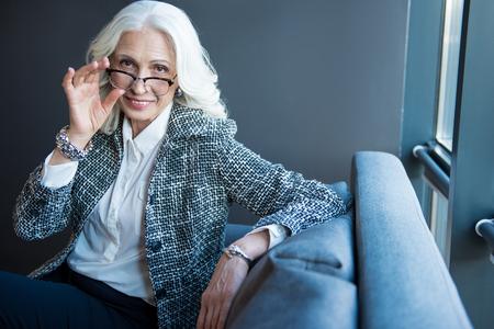 Positive senior elegant businesswoman is sitting on sofa