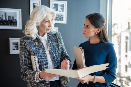 Confident elegant aged lady is standing with younger woman