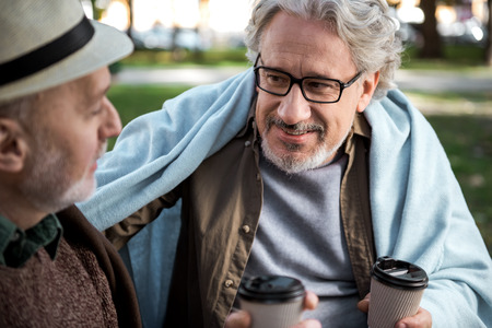 Portrait of cheerful mature man supporting his friend by positive conversation. They are holding cup of coffee and smiling