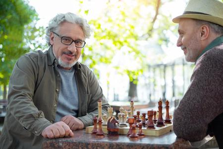 Joyful senior male chess players resting in park