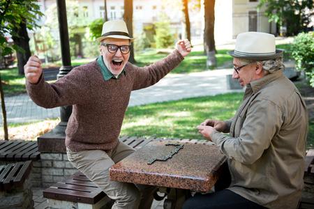 Cheerful senior pensioner winning dominoes game Stock Photo
