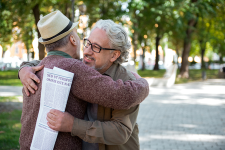 Cheerful senior comrades greeting each other outdoor Stock Photo