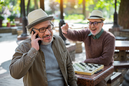 chequer: Happy mature male pensioner communicating on cellphone